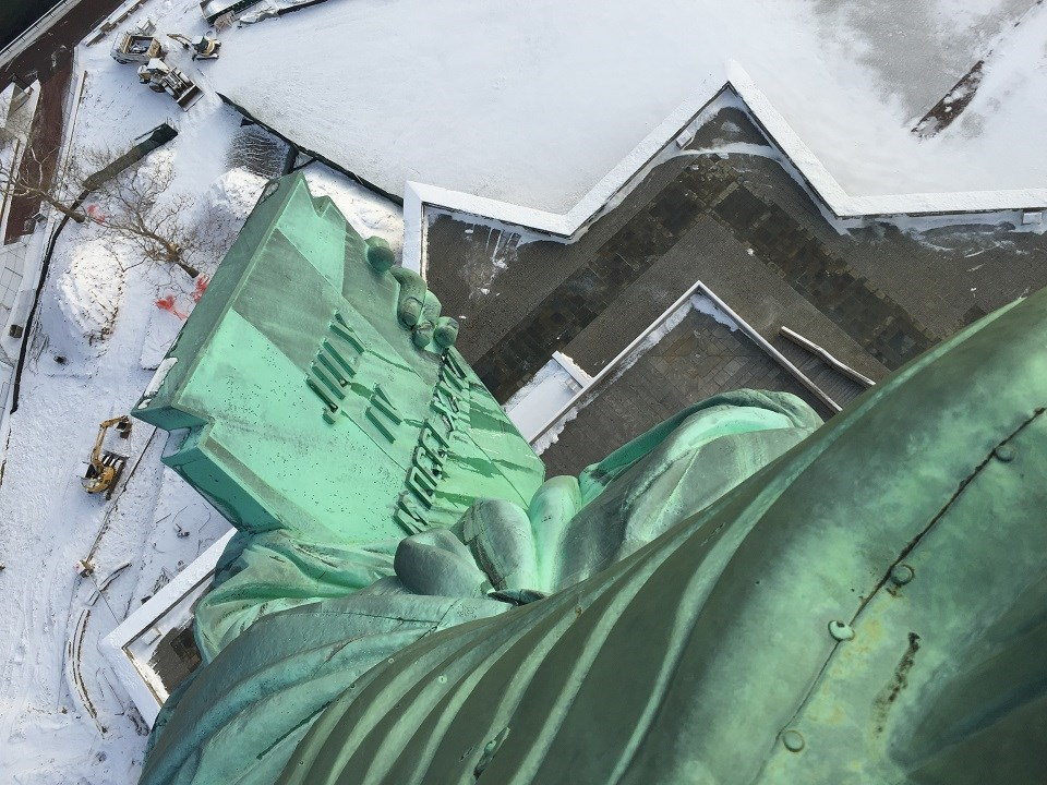 The Statue of Liberty's tablet looking out and down the windows of the crown during the winter. The ground is white, covered in snow.