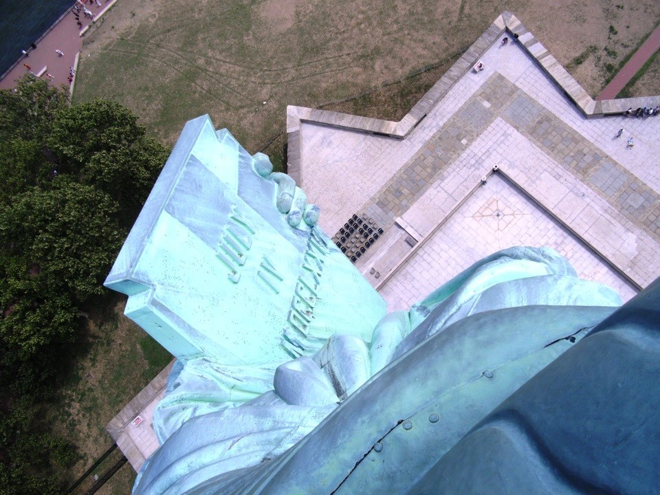 The Statue of Liberty's tablet looking out and down the windows of the crown. It's a sunny day and the grass and trees are green.