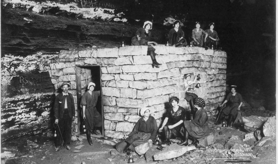 Ten young women and one man posed on and around a small stone building inside Mammoth Cave.