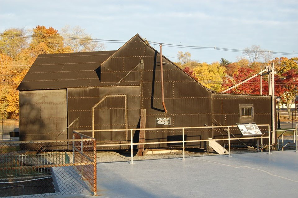 A viewing deck leads to a windowless structure, covered by black tar paper.
