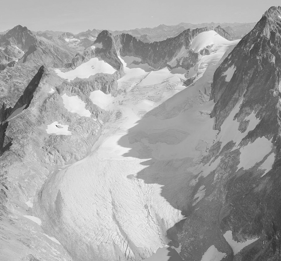 Black-and-white photo of a glacier extending to the bottom of the frame
