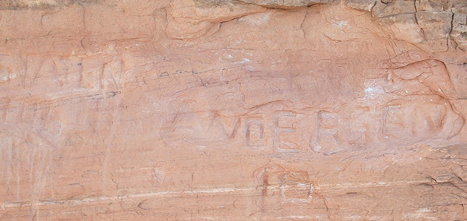 a rock wall with carved letters in it