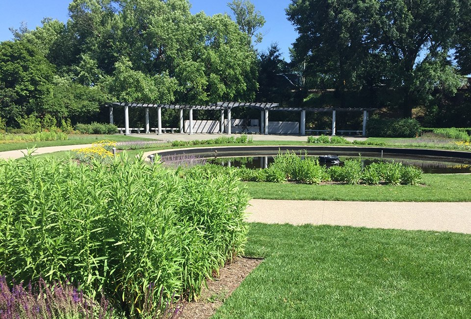 George Mason Memorial in summer. Lush green grass and plants surround a pool of water.