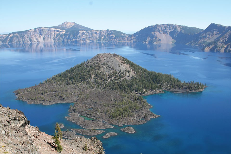 mountain top lake with volcanic cone island