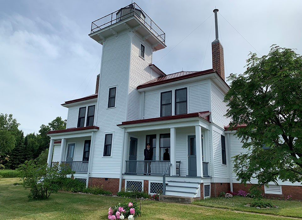 Two story white house, side by side duplex style with a central lighthouse tower.