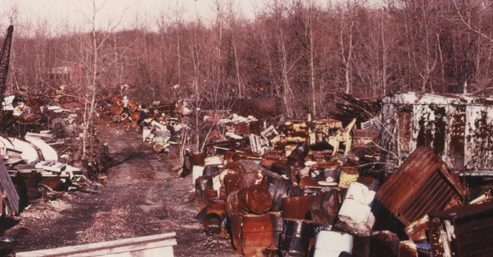 An unpaved road through tall stacks of metal and wooden debris mixed with old tires and rusting drums. Bare trees line the edges of the dump.