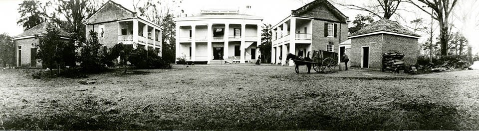 Historic image of the backyard of the Melrose Estate with a horse and cart in a building-encircled courtyard.