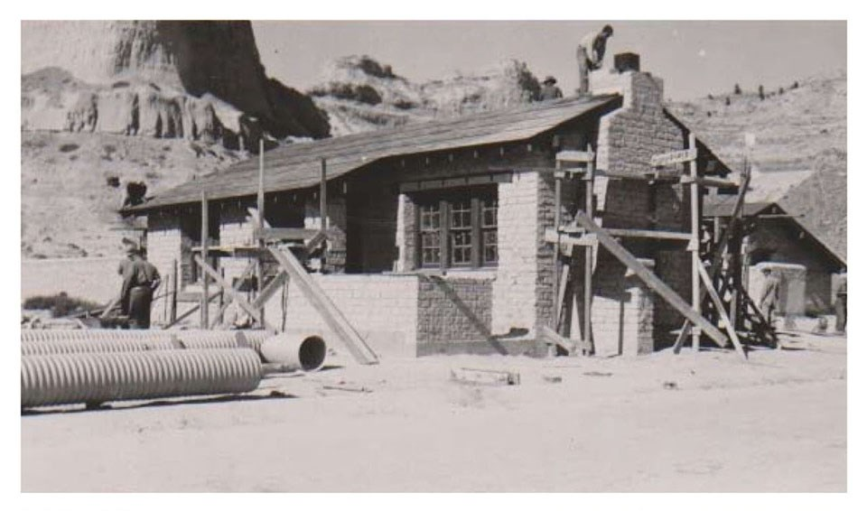 The scaffolding, drainpipes, and workers show the construction that is occurring on an adobe brick structure.