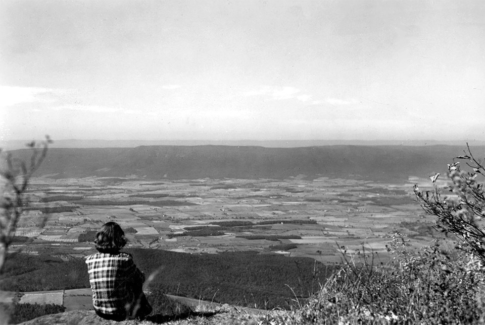 Black and white photo of a person sitting overlooking a valley