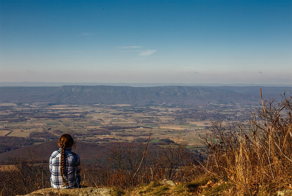Person sitting overlooking a valley
