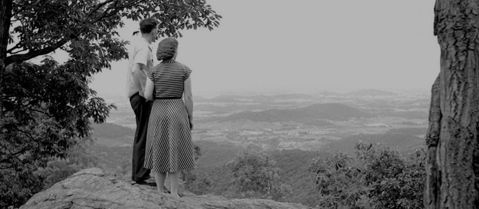 Black and white photo of a couple standing on an outcrop overlooking a valley