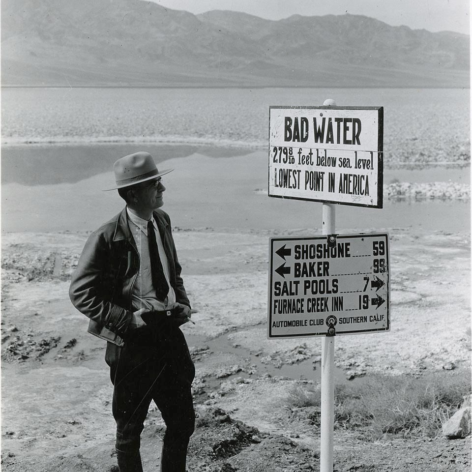 A ranger in 1935 stands next to a sign that reads Badwater 279 feet below sea level