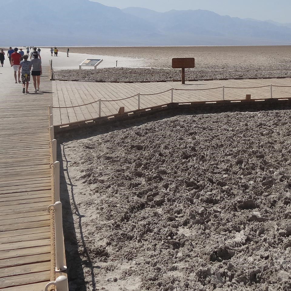 The wooden boardwalk at badwater streches into the white salt flat with mountains in the background.