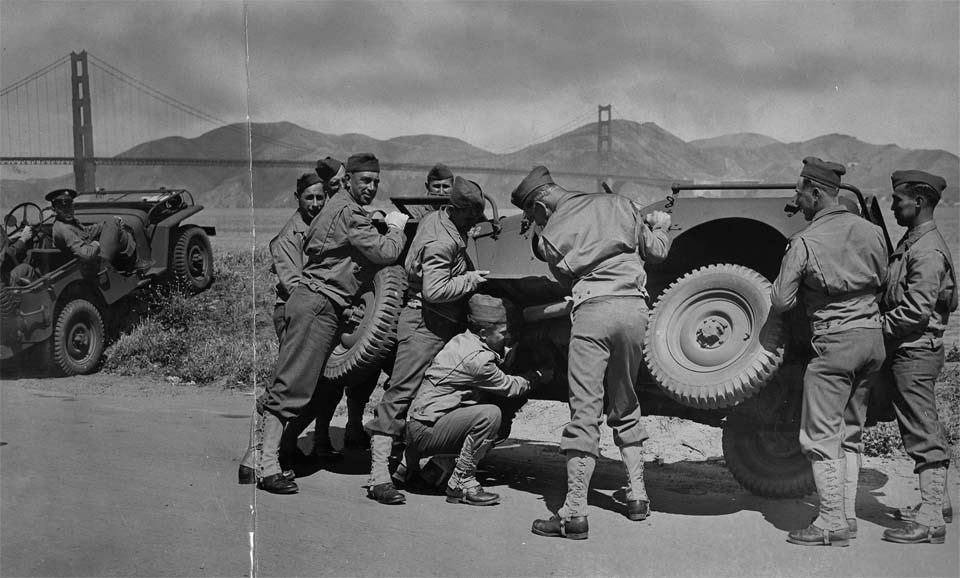 soldiers attempt to repair a jeep with the golden gate bridge in the background