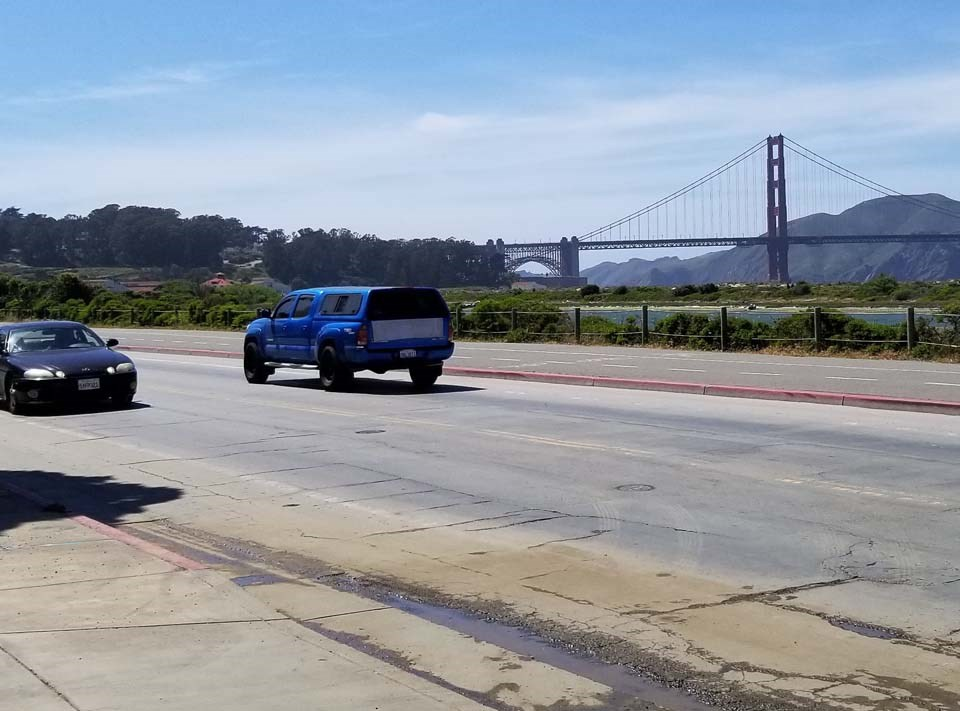 cars on the street with the golden gate bridge in the background