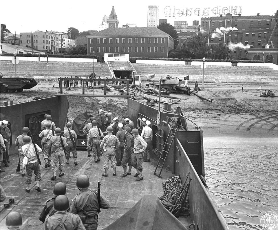 Historic photo of soldiers in a boat with Ghirardelli in the background