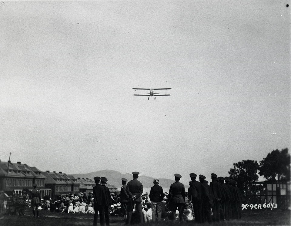 Photo of a biplane flying over the Presidio 1929