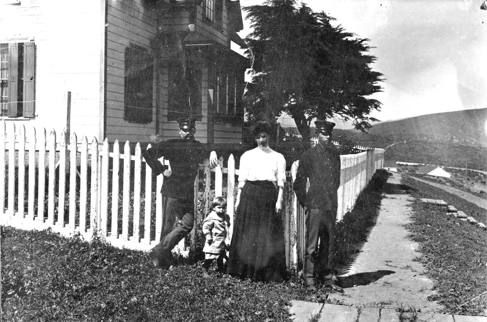 people posing in front of a cottage