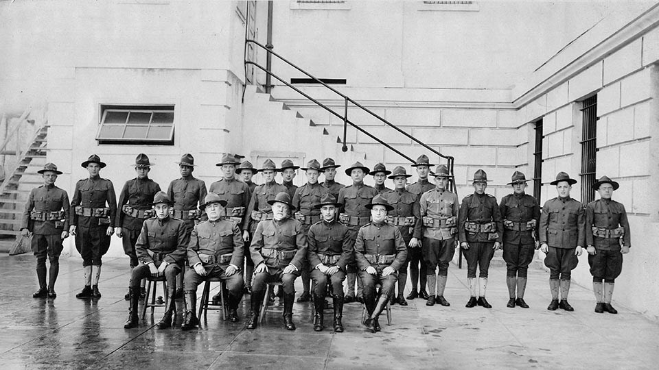 military staff pose in front of stairs outside of concrete building