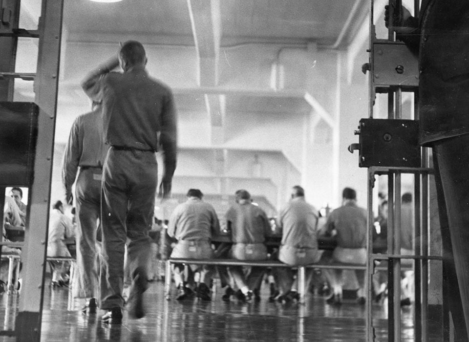 Guard stands at cell doors of crowded Alcatraz prison dinning hall