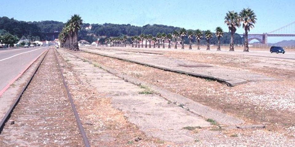 Image of crissy field before restoration: train tracks and empty land with little to no vegetation.