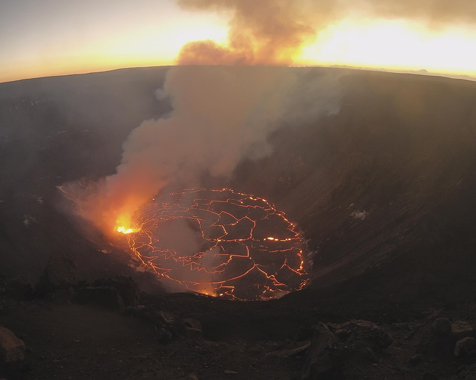 Steaming and glowing lava lake in a volcanic crater