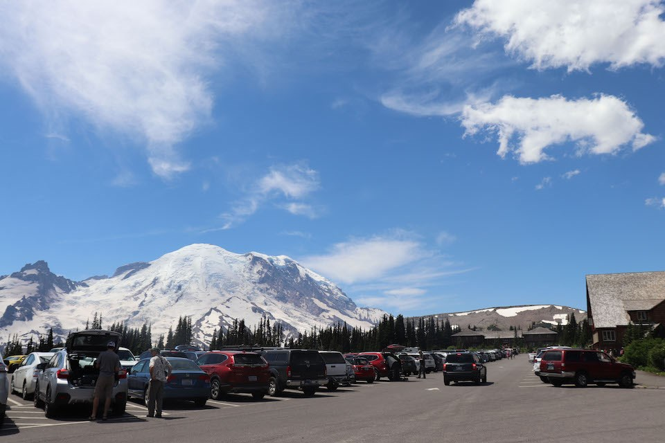A parking lot full of cars and people with a sunny sky and Mount Rainier in the back.