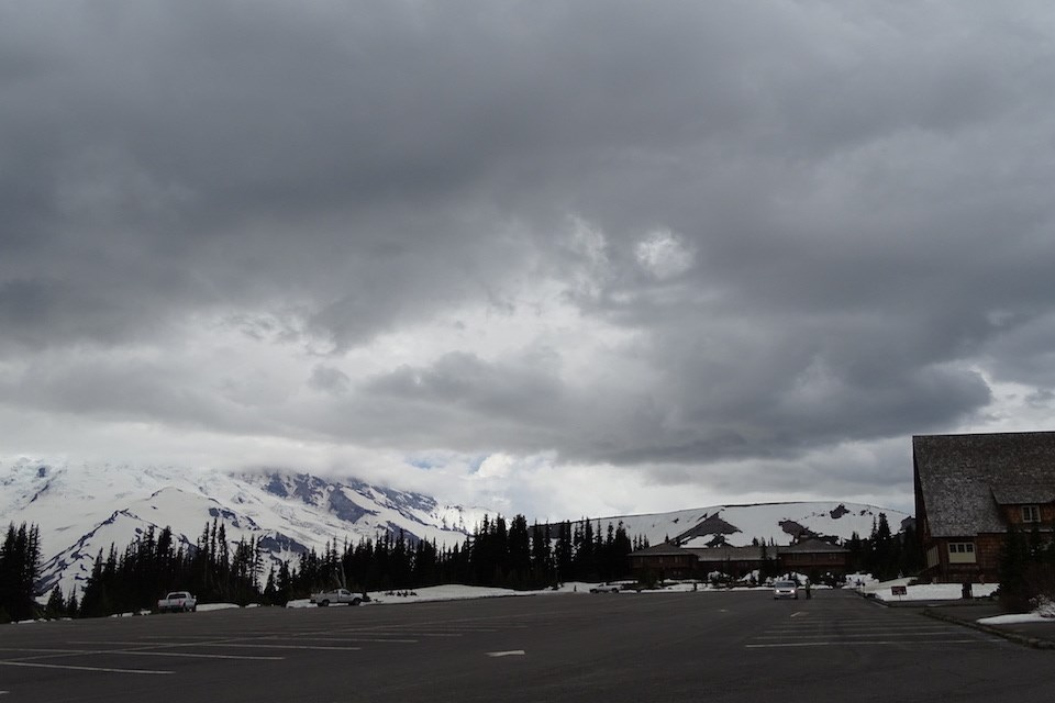 An empty parking lot with a cloudy sky covering Mount Rainier from view in the background.