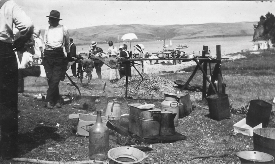 A black and white photo of a cookout attended by men and women on a beach as boats float in the bay in the background.