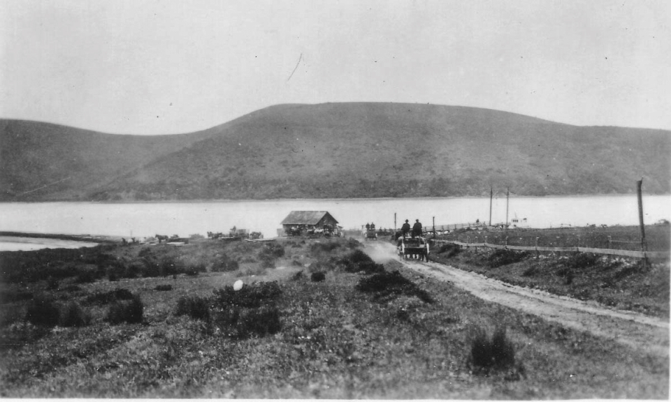 A black and white photo of horse-drawn wagons traveling along a dirt road that leads to a building and a dock on a body of water with hills in the background.