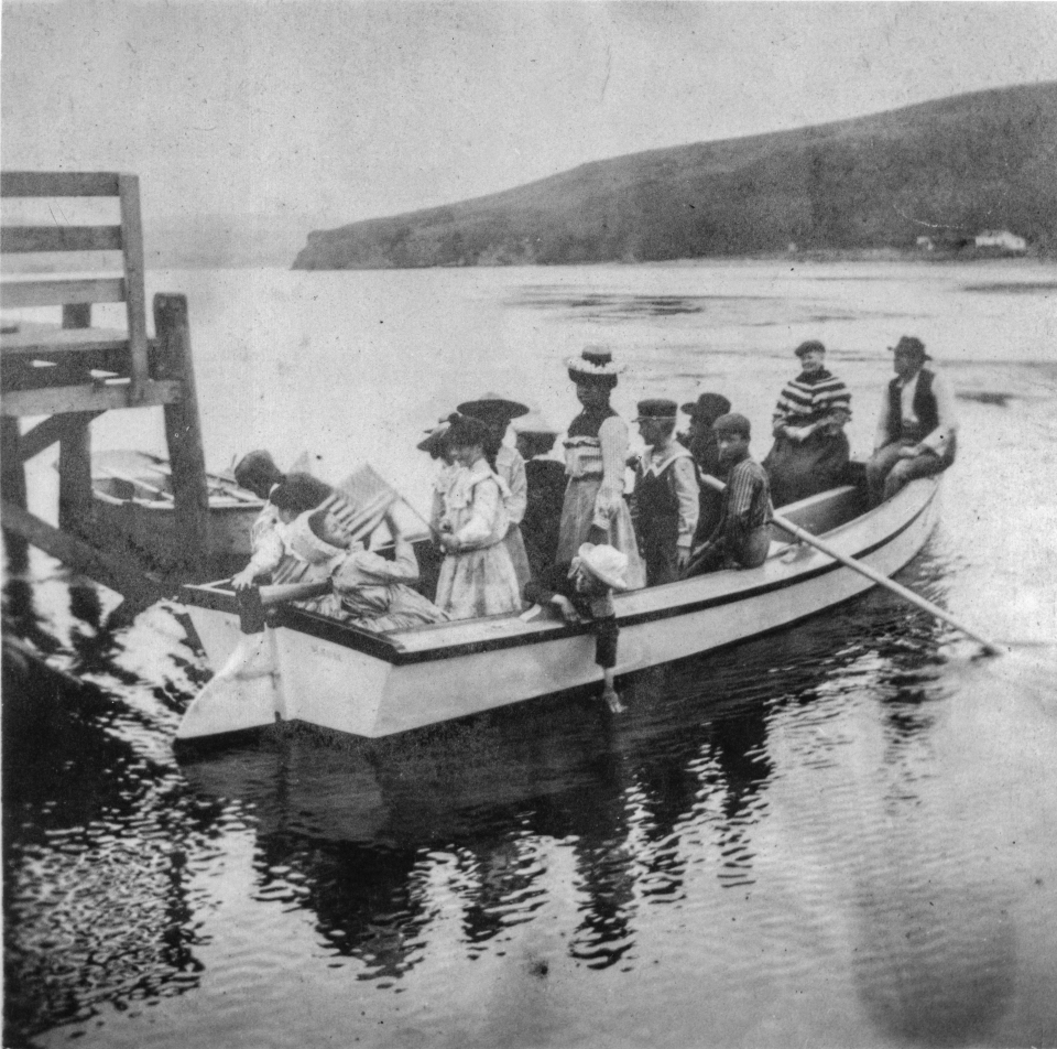 A black and white photo of thirteen people in a rowboat adjacent to a dock on the left. Low headlands rise above the far end of the bay.