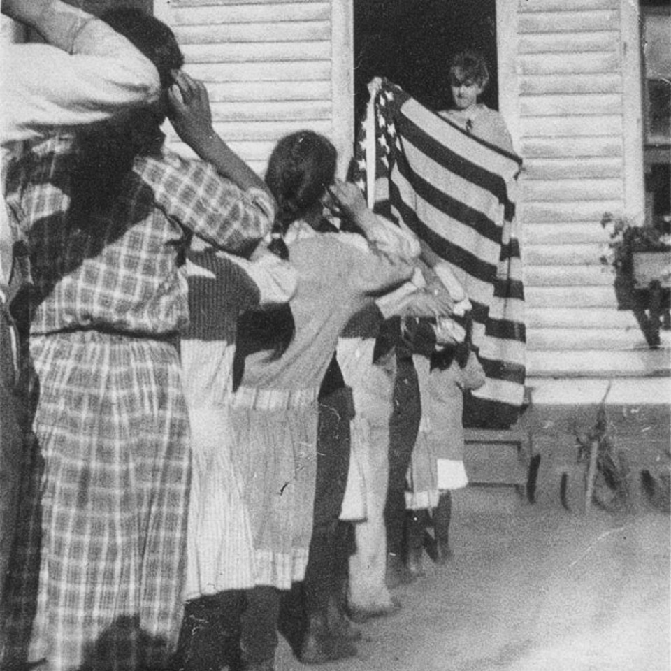 A black and white photo of a teen-aged boy holding an American flag while standing in a doorway of a white building as a line of children salute the flag. children, a flag, and school house.
