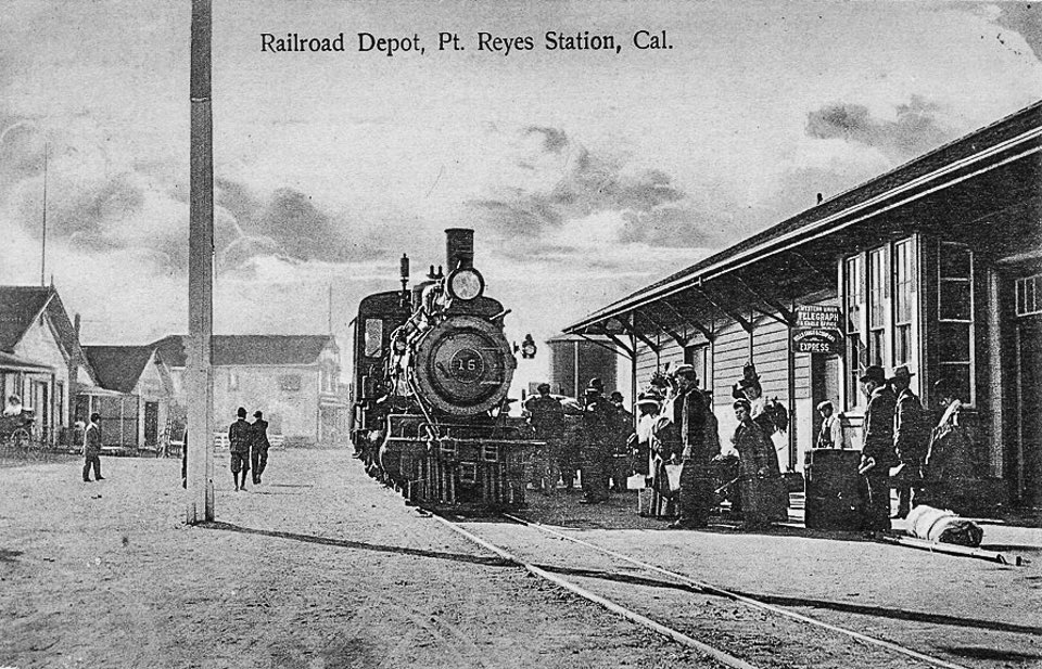 A black and white photo of people milling about a steam locomotive that is parked on tracks adjacent to a one-story-tall train station on the right and a dirt road on the left.