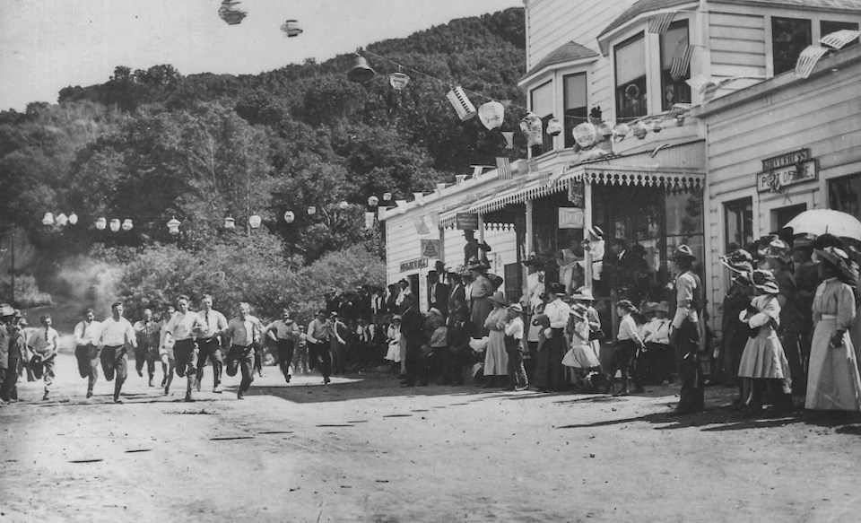 A black and white photo of eleven young men running a race on a dirt road past with a crowd of people and buildings in the early 1900s.