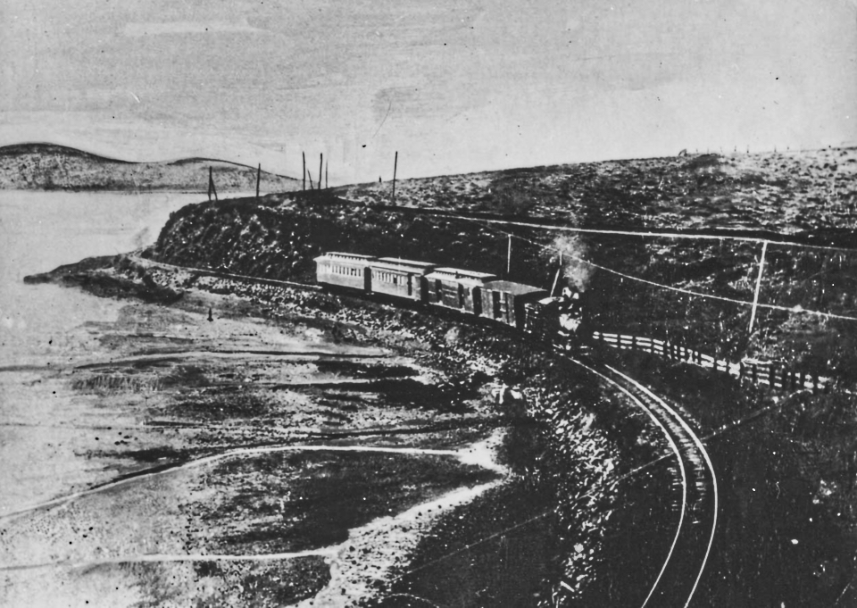 A black and white photo of a steam locomotive pulling four cars on railroad tracks that wind along a bay on the left.