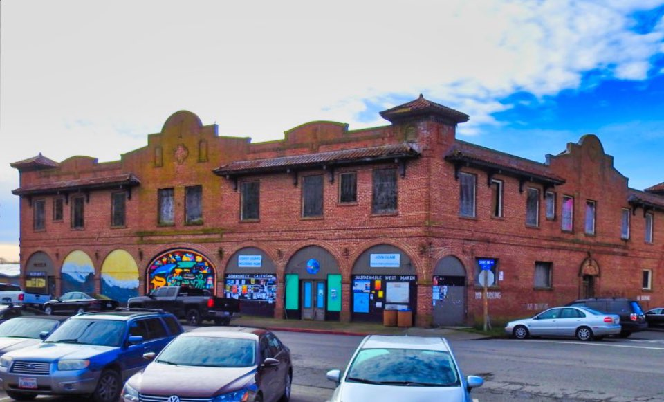 A color photo of a two-story-tall brick building. Seven arches along its facade have been covered with plywood, upon which murals have been painted and flyers and bulletin boards have been placed. Modern automobiles are visible in the foreground.