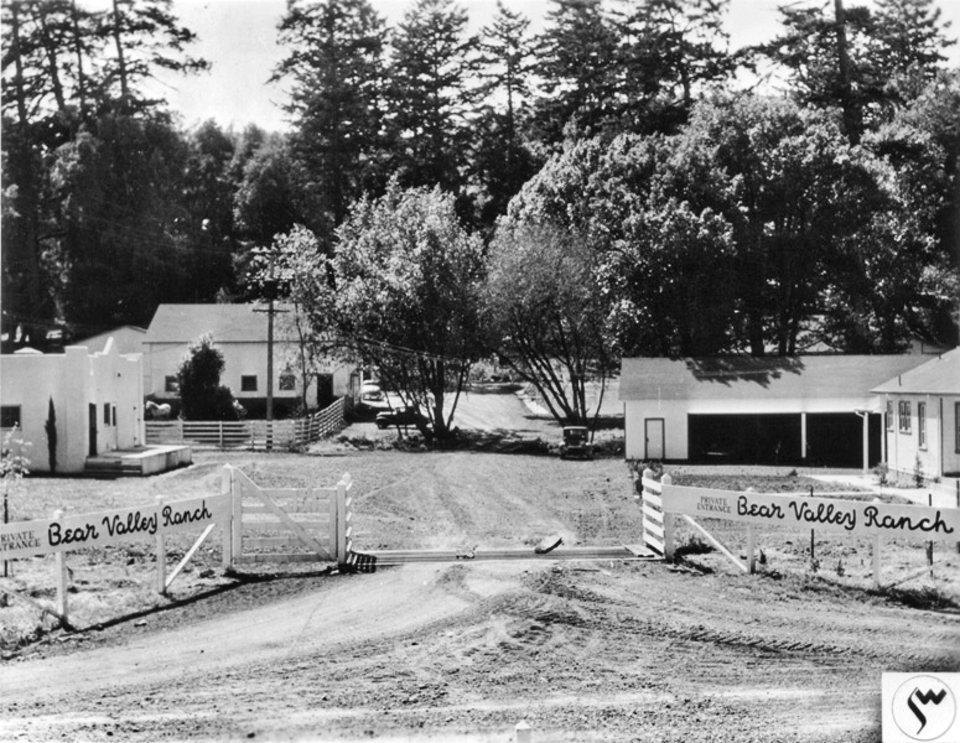 "A black and white photo of dirt driveway passing over a cattle guard. Painted on white fences on both sides of the driveway is ""Private Entrance. Bear Valley Ranch."" Beyond the cattle guard are a number of white buildings, beyond which are tall trees."