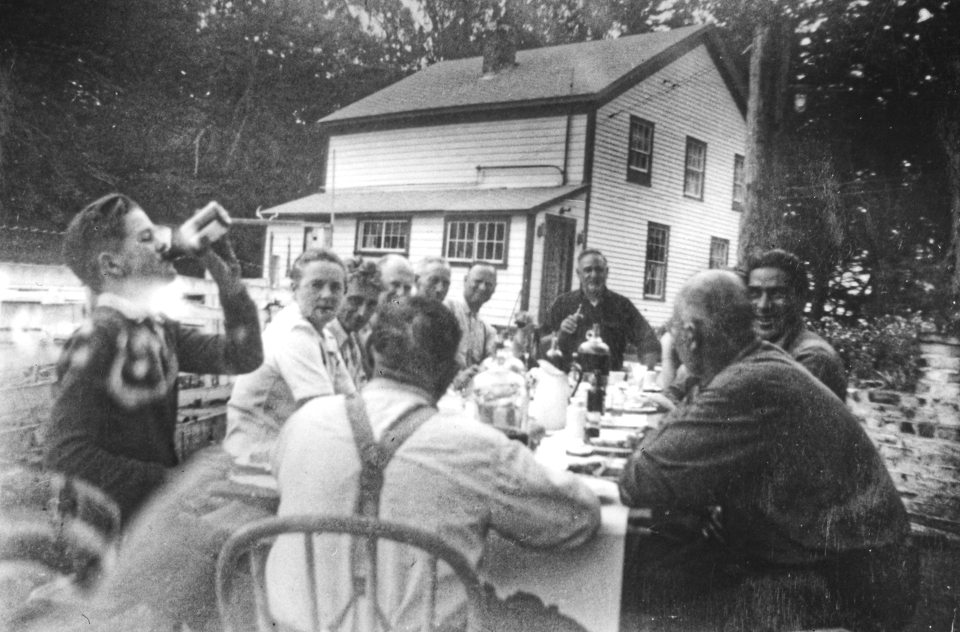 A black and white photo of men sitting outside at a table eating with a building behind them.
