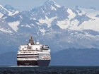 a large cruise ship on the ocean with snowy mountains in the distance