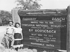 Two visitors pose by a sign for Faraway Ranch advertising horseback rides to see Chiricahua NM