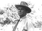 Portrait of Ed Riggs in a shirt and tie, and wearing a brimmed hat