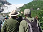 a ranger next to a visitor points towards a mountain slope with a glacier in the background.