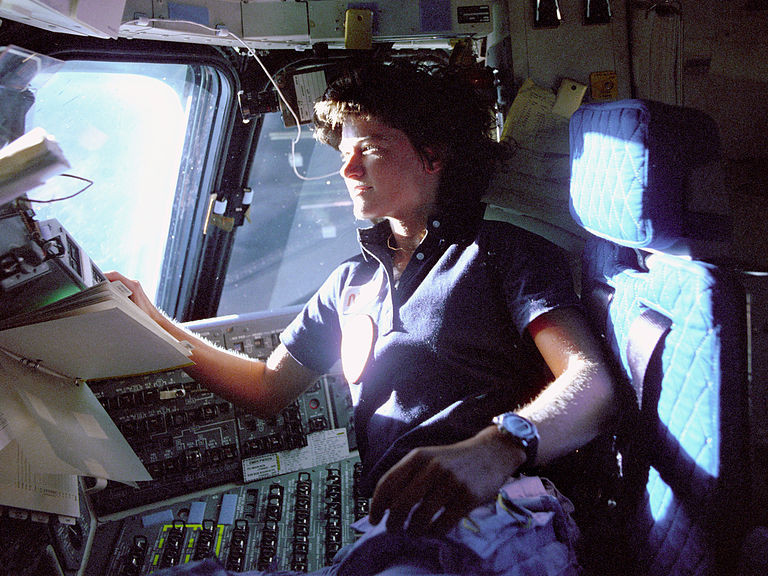 In orbit above the Earth, Sally K. Ride monitors flight status from the Space Shuttle Challenger