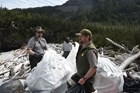 park rangers putting trash into white plastic bags on a rocky beach