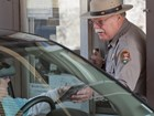 A park ranger speaks with visitors in a car