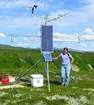 A woman with long, dark hair, lilac shirt and jeans stands next to a climate monitoring station.