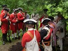 Soldiers in Red Coat and tricorn hats with heads bowed around a grave