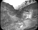 Black and white historic photo of a side canyon with a creek between towering cliffs.