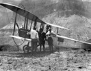 Old fashioned biplane with pilots standing nearby.