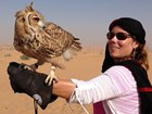 woman wearing black headscarf holding an owl on her outstretched gloved arm.